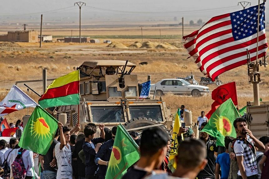 Syrian Kurds gather around a US armoured vehicle during a demonstration against Turkish threats next to a base for the US-led international coalition on the outskirts of Ras al-Ain town in Syria's Hasakeh province near the Turkish border on Oct 6, 20