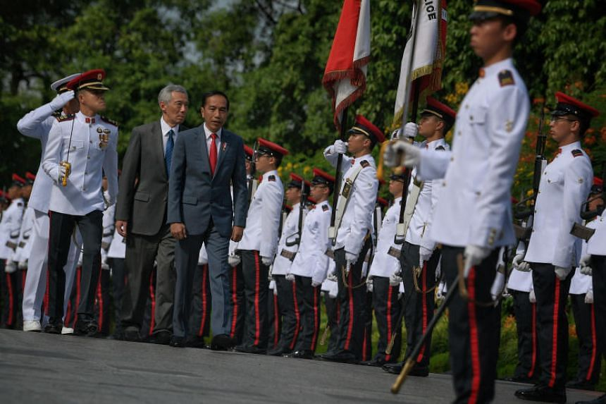 Prime Minister Lee Hsien Loong and visiting Indonesian President Joko Widodo inspect the guard of honour during the welcome ceremony ahead of the Singapore-Indonesia Leaders' Retreat at the Istana on on Oct 8, 2019.