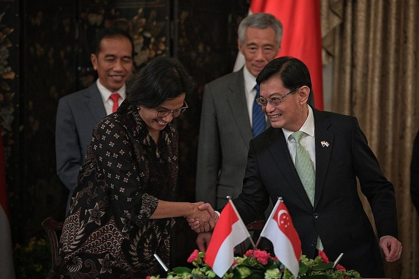 Finance Minister Heng Swee Keat, who is also Deputy Prime Minister, and his Indonesian counterpart Sri Mulyani Indrawati after signing a pact yesterday on the electronic exchange of trade data between their countries. The signing was witnessed by Ind
