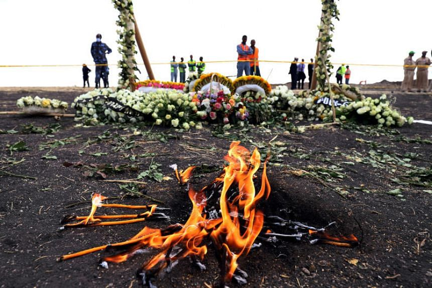 In this photo taken on March 14, 2019, candle flames burn during a commemoration ceremony for the victims at the scene of the Ethiopian Airlines Flight ET 302 plane crash.