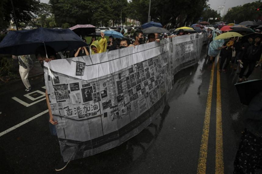 "Protesters in Taipei carry a makeshift ""Lennon Wall"" banner as they march in the street to show their support for the Hong Kong protests, on Sept 29, 2019."