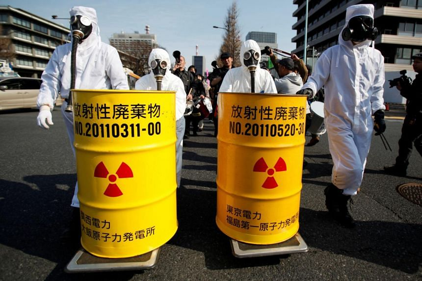 Anti-nuclear protesters wearing protective suits push mock drums labelled as radioactive waste at a protest in Tokyo in 2014.