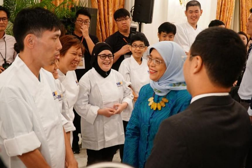 President Halimah Yacob (in blue) and Minister for Social and Family Development Desmond Lee (foreground, in black) mingle with Community Chest beneficiaries at the Community Chest Awards at the Istana on Oct 9, 2019.