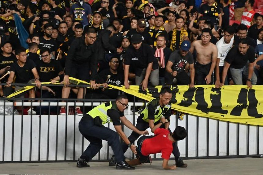 Police officers detain an Indonesia team supporter while Malaysia team supporters (in black) look on, during a 2022 Qatar World Cup preliminary qualification match in Jakarta on Sept 5, 2019.