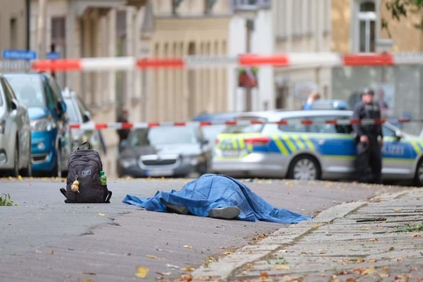 A body laying in the street is covered as police block the area around the site of a shooting in Halle, Germany, on Oct 9, 2019.