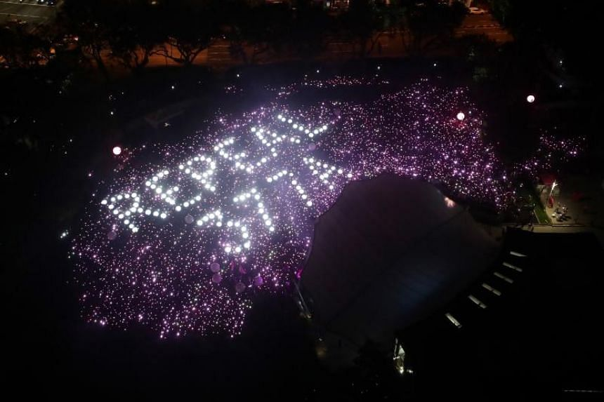 "In this file picture, attendees of The Pink Dot SG event at Hong Lim Park on June 29, 2019 are seen holding up pink and white lights to form a display calling for the repeal of Section 377A, which criminalises acts of ""gross indecency"" between men."