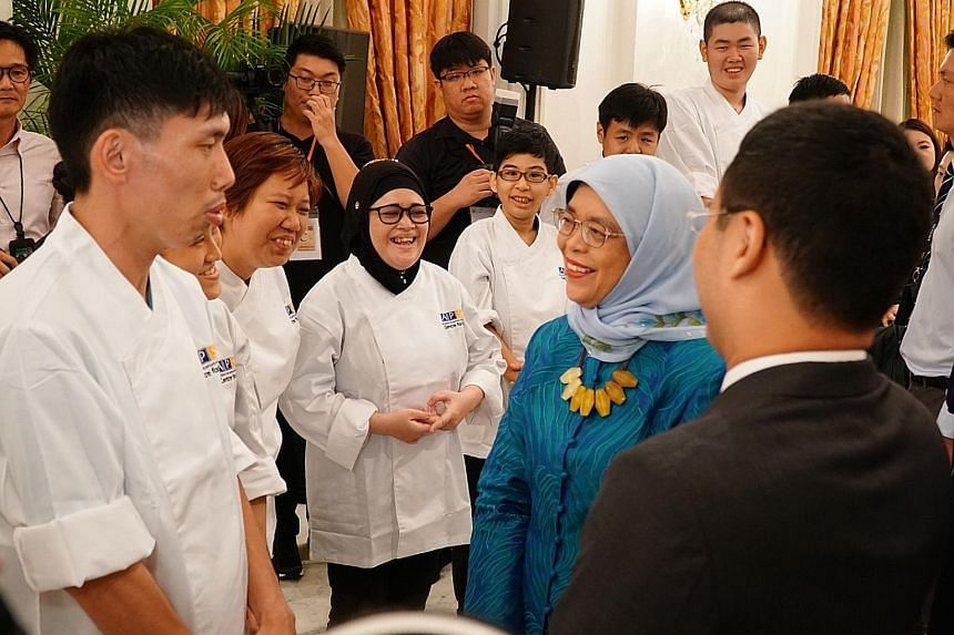 President Halimah Yacob and Minister for Social and Family Development Desmond Lee talking to students from the Association for Persons with Special Needs, one of the beneficiaries of the Community Chest, at the awards event at the Istana yesterday.