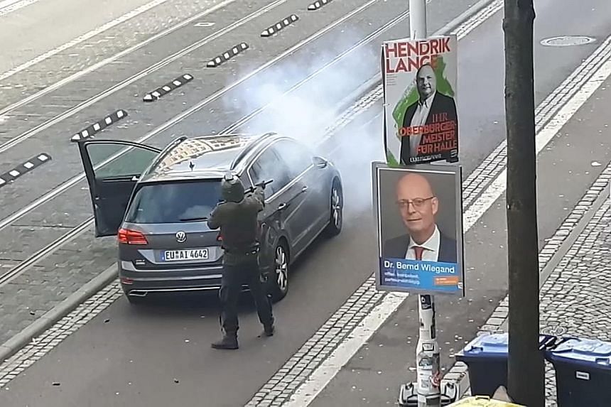 Footage from an amateur video showing the shooter firing at a car in the German city of Halle. One of the assailants was arrested, while two others remain at large.