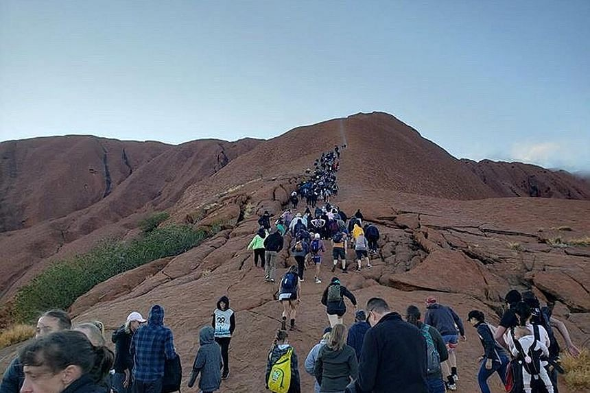 Tourists crowding a trail as they attempt to climb Uluru in Australia's Northern Territory before an Oct 26 ban takes effect.