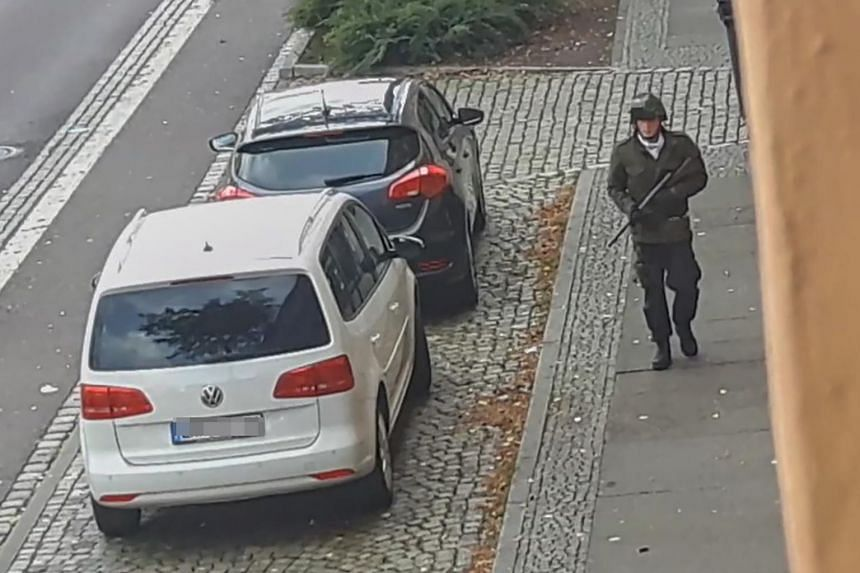 In this screenshot taken from a video by ATV-Studio Halle, a man walks with a gun in the streets of Halle an der Saale, eastern Germany on Oct 9, 2019.