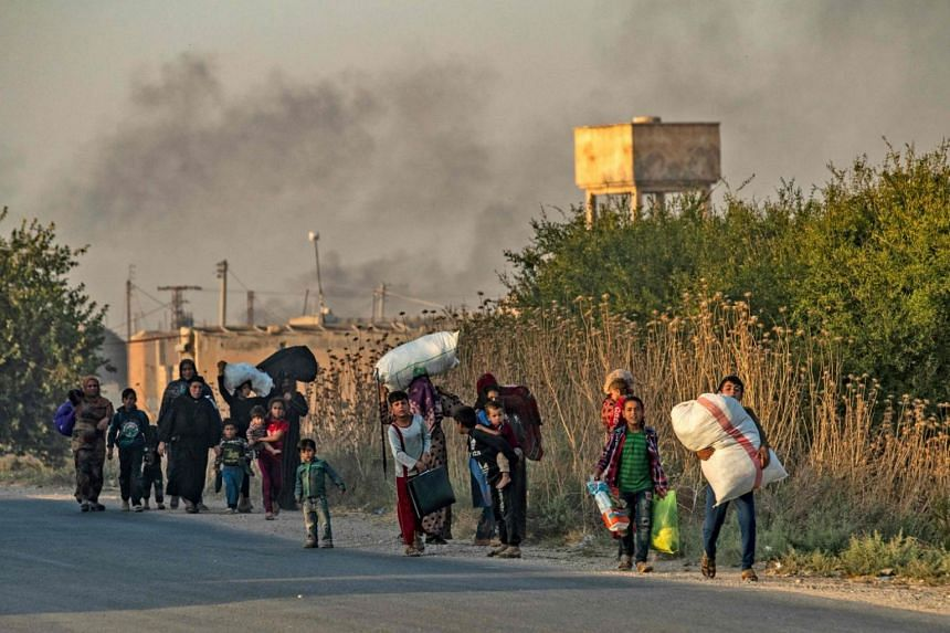 Civilians flee with their belongings amid Turkish bombardment on Syria's northeastern town of Ras al Ain in the Hasakeh province along the Turkish border on Oct 9, 2019.