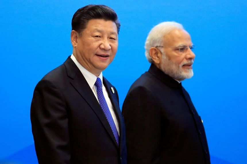 Chinese President Xi Jinping and Indian Prime Minister Narendra Modi arrive for a signing ceremony during the Shanghai Cooperation Organization (SCO) summit in Qingdao, China on June 10, 2018.