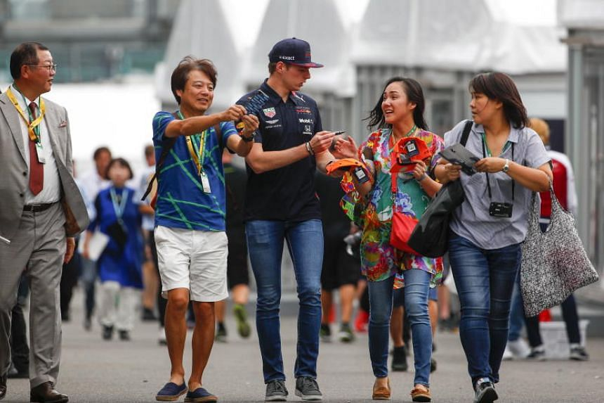 Red Bull's Max Verstappen signs autographs for fans on the paddock at the Suzuka circuit on Oct 10, ahead of the Japanese Formula One Grand Prix.