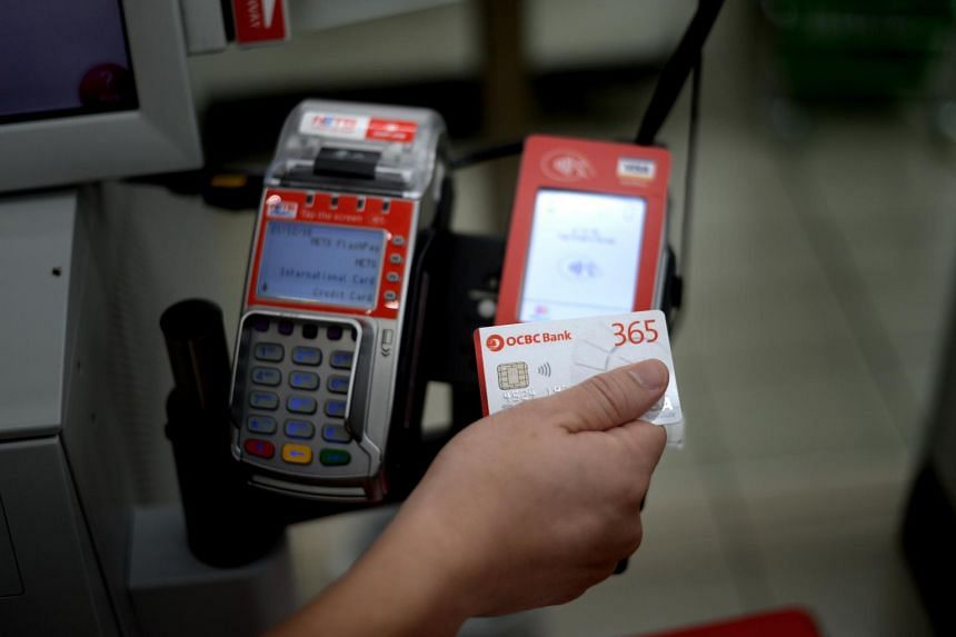 A customer using Visa payWave to pay at a self checkout counter at NTUC Fairprice.