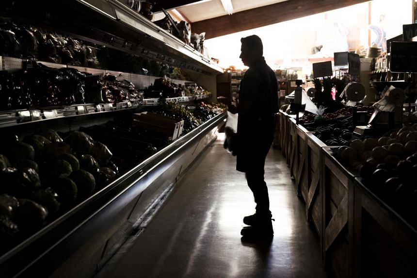 A customer shops for groceries at La Tapatia Market during a blackout in Napa, California on Oct 9, 2019.