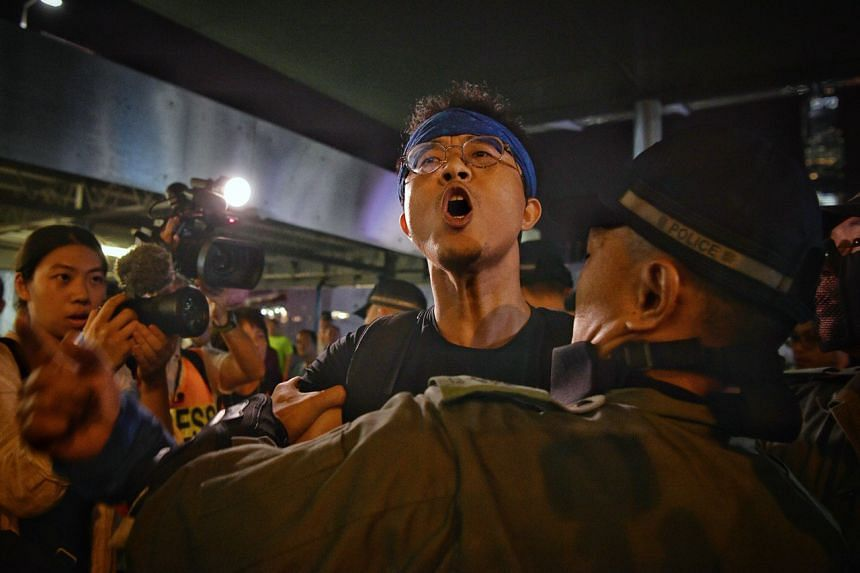 Hong Kong police stop a pro-China supporter from clashing with pro-democracy protesters at Harbour City on Oct 10, 2019.