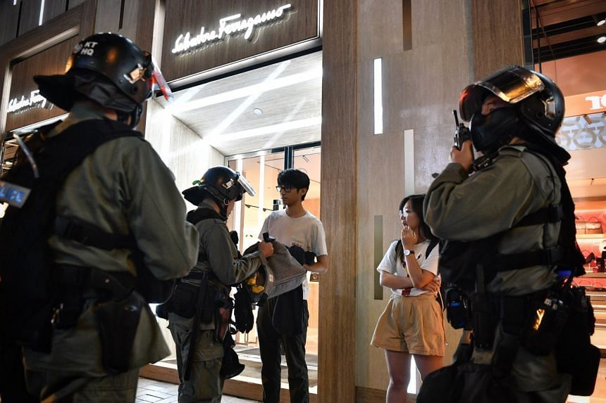 Hong Kong police stopping and searching two people who were wearing face masks at Harbour City in Tsim Sha Tsui on Oct 10, 2019.
