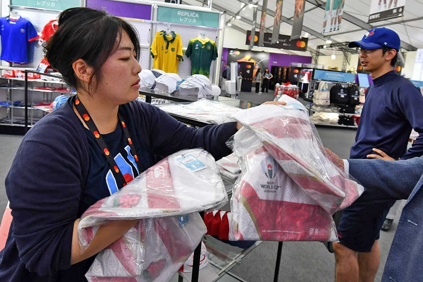 A worker putting replicas of Japan's red-and-white jersey on the shelves at the Rugby World Cup megastore in Tokyo. PHOTO: AGENCE FRANCE-PRESSE