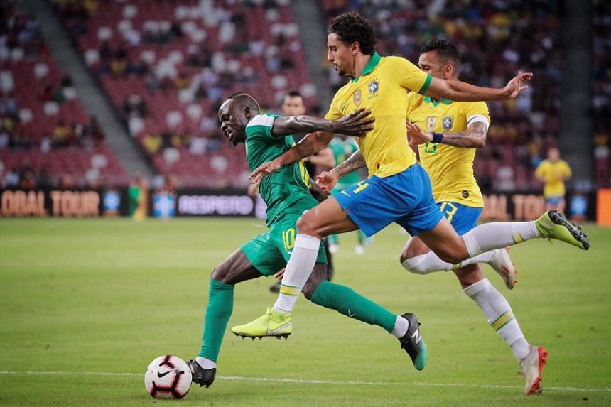 Senegal's Sadio Mane (left) wins a penalty as he is challenged by Brazil's Marquinhos (centre) and Dani Alves (right) as Brazil take on Senegal during their international friendly football match at the National Stadium in Singapore on Oct 10, 201