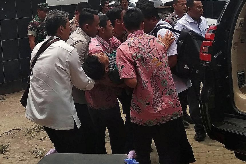 Indonesia's chief security minister Wiranto being carried from a car to the emergency room yesterday after he was attacked in Pandeglang, on Java Island. He was treated for two knife wounds in his stomach. PHOTO: REUTERS