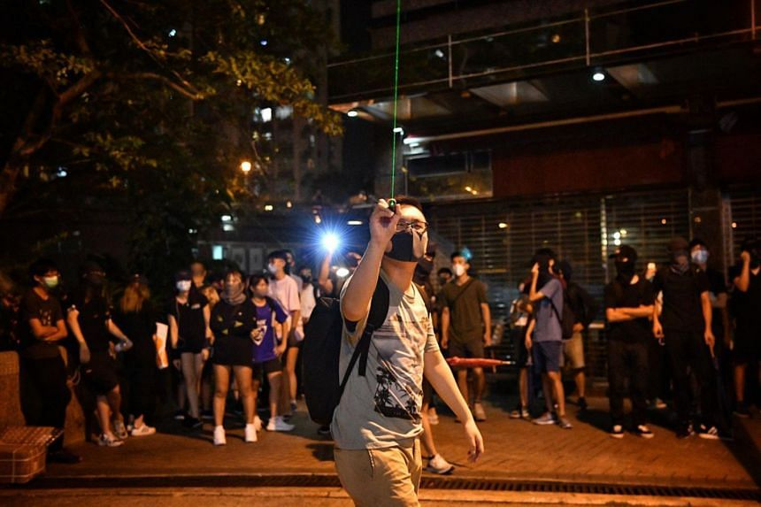 A protester points a laser pointer at Ma On Shan Police Station on Oct 9, 2019.