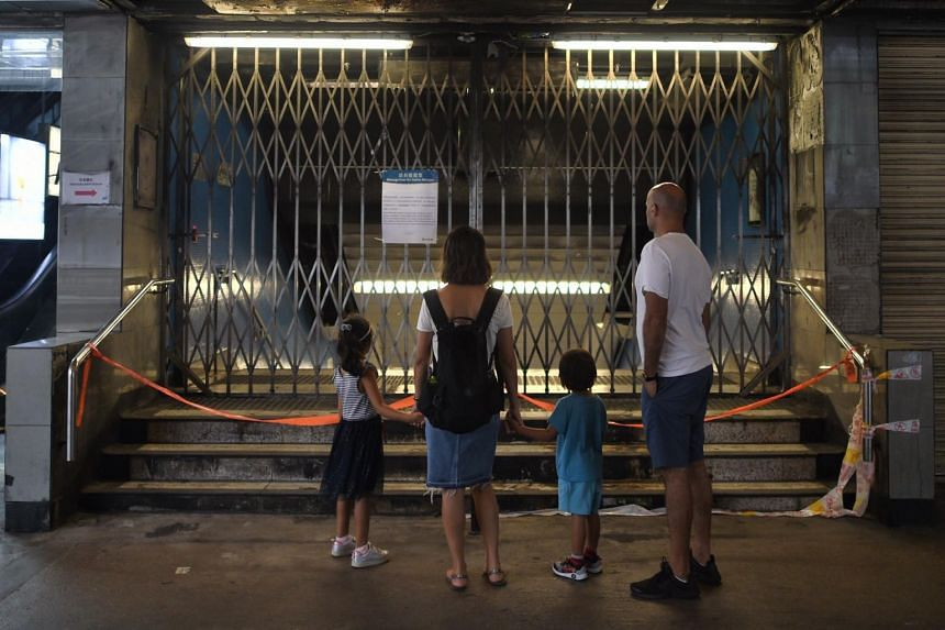 A family stands outside the charred and shuttered exit of Admiralty MTR station on Oct 6. Protesters have targeted the MTR because it has been blamed for closing stations on the government's behalf to contain demonstrations.