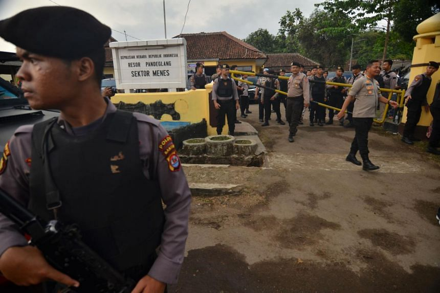 Indonesian security block off the scene after two Indonesians stabbed the country's chief security minister Wiranto in Pandeglang, Java on Oct 10, 2019.