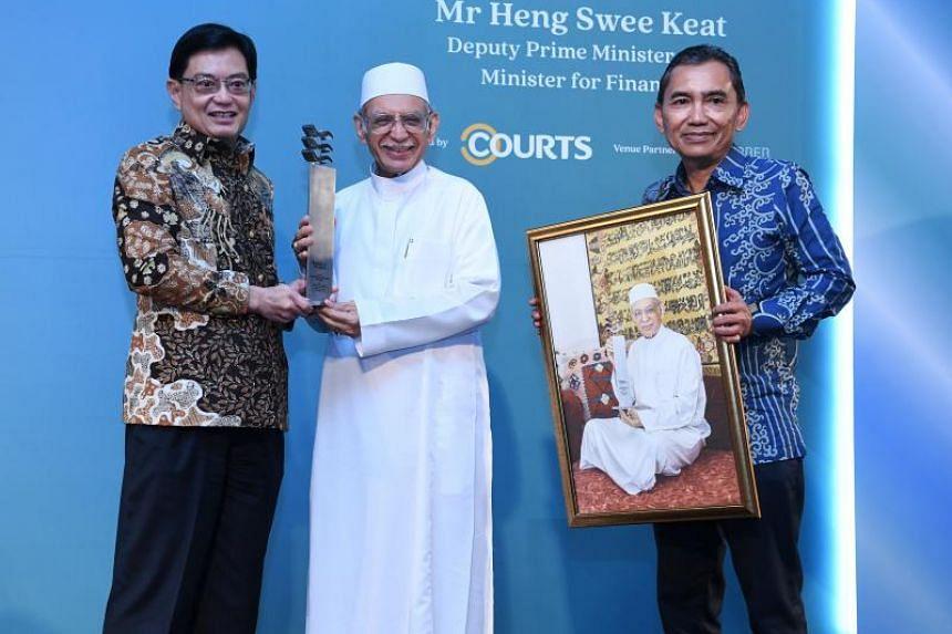 Habib Hassan Al-Attas (centre) receives the Berita Harian Anugerah Jauhari from DPM Heng Sweet Keat. With them is Editor of Berita Harian, Mr Saat Abdul Rahman.