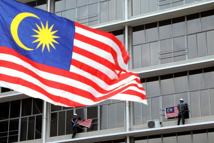 A photo taken in Kuala Lumpur on Aug 31 shows workers hanging Malaysian flags ahead of celebrations for the country's 62nd anniversary of independence.