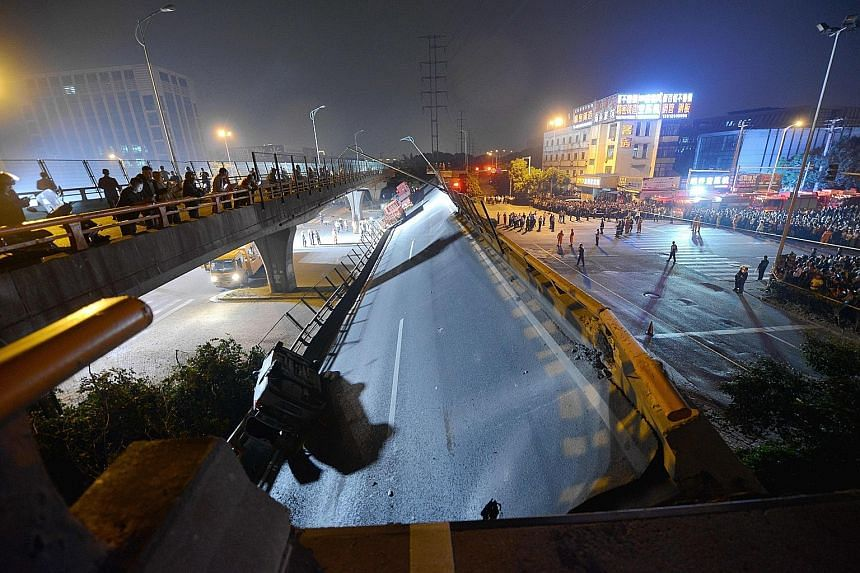 Rescuers working beside the collapsed highway overpass in Wuxi, China's Jiangsu province, on Thursday night. A preliminary investigation showed the collapse had been caused by an overloaded truck.