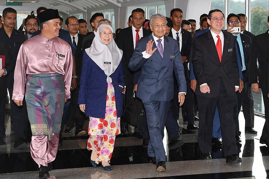 Malaysia's Prime Minister Mahathir Mohamad waving on arrival at Parliament for the budget presentation by Finance Minister Lim Guan Eng (right) yesterday. Accompanying them were Deputy Finance Minister Amiruddin Hamzah and Deputy Prime Minister Wan A