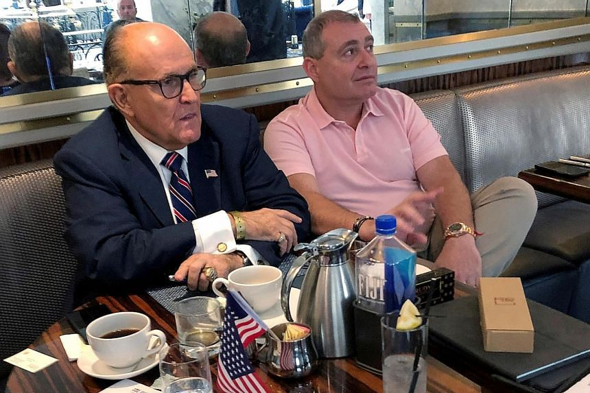 President Donald Trump's personal lawyer Rudy Giuliani (far left) with Lev Parnas last month. Parnas and Igor Fruman (above) were arrested on Wednesday after trying to board a flight out of the US on one-way tickets. PHOTOS: REUTERS