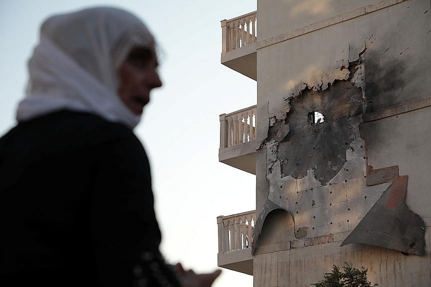 An apartment building in Nusaybin, Turkey, damaged by a rocket fired from Syria on Thursday. Overnight, clashes erupted at different points along the border, with Turkish and Kurdish-led Syrian Democratic Forces (SDF) exchanging shelling, said a spok