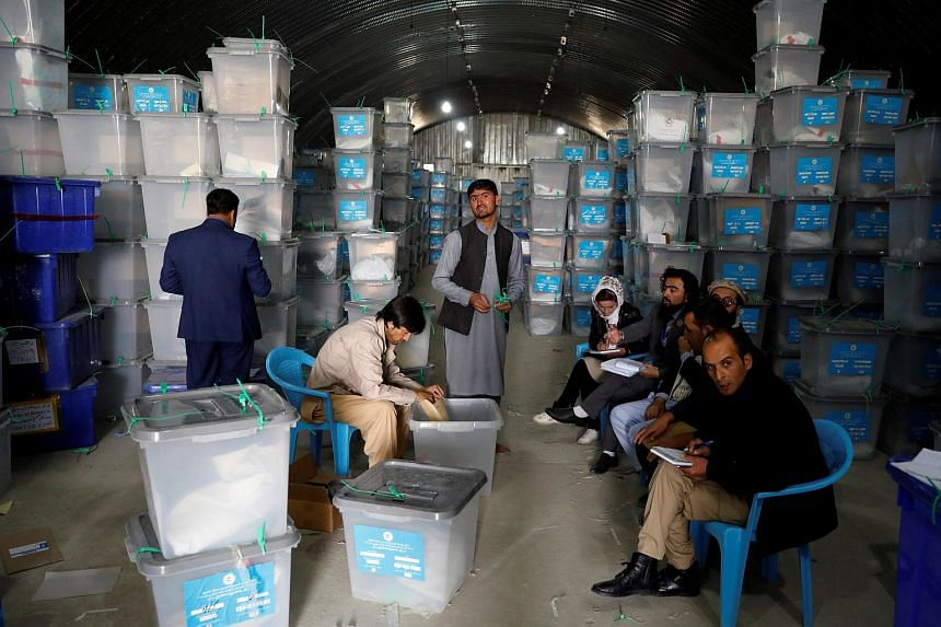 """Afghan election commission workers opening ballot boxes at a warehouse in Kabul on Oct 7, 2019. The running mate of a top candidate in Afghanistan's elections is alleging """"systemic fraud"""" by the country's election commission."""
