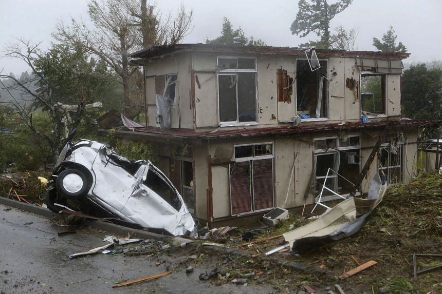 A damaged vehicle is seen in a ditch next to a badly damaged house after strong winds brought by Typhoon Hagibis Ichihara, Chiba prefecture, on Oct 12, 2019.