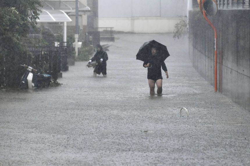 People walking through a flooded road after heavy rainfall brought by Typhoon Hagibis hit Shizuoka, on Oct 12, 2019.