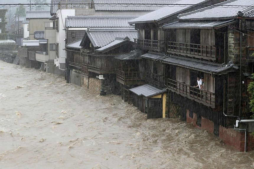 Men watching the swollen waters of the Isuzu River in Ise, central Japan, after heavy rainfall caused by Typhoon Hagibis, on Oct 12, 2019.