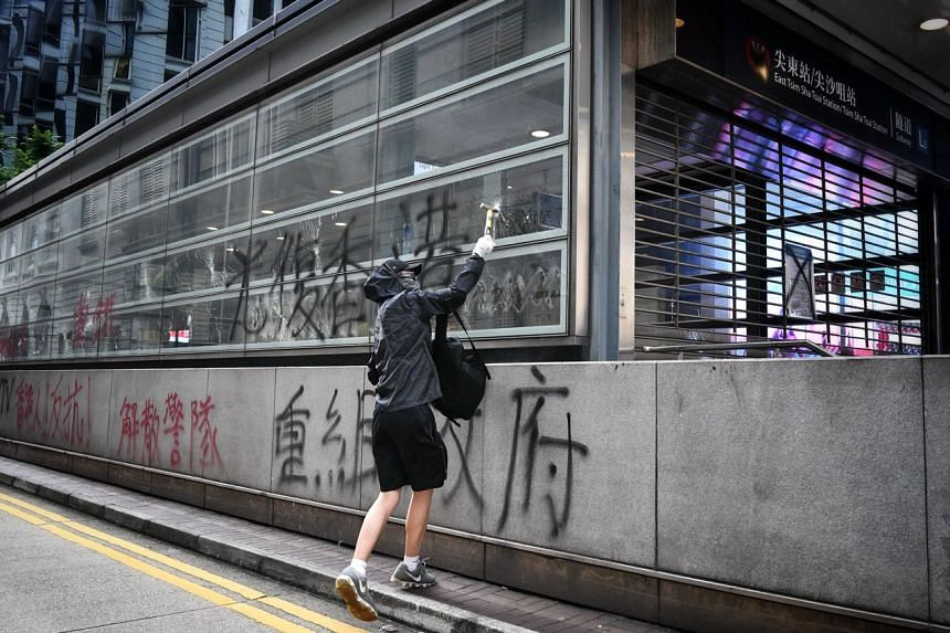 A protester hammering glass panes at East Tsim Sha Tsui station in Hong Kong on Oct 12, 2019.