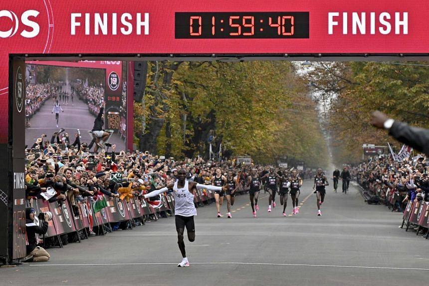 Kenya's Eliud Kipchoge celebrating as he crosses the finish line at the end of his attempt to bust the two-hour barrier for the marathon, in Vienna on Oct 12, 2019.