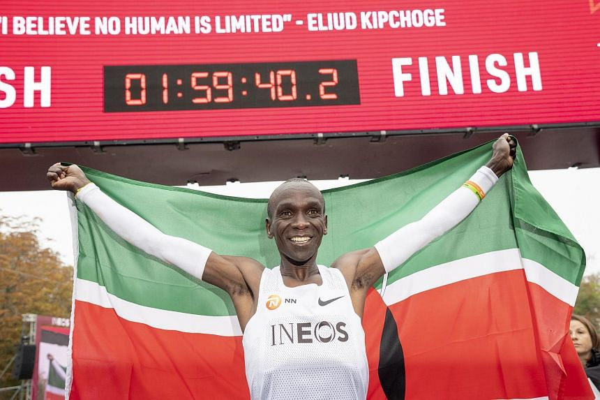 Eliud Kipchoge celebrating with the Kenyan flag after crossing the finish line with a time of 1hr 59min 40sec, in Vienna, Austria, on Oct 12, 2019.