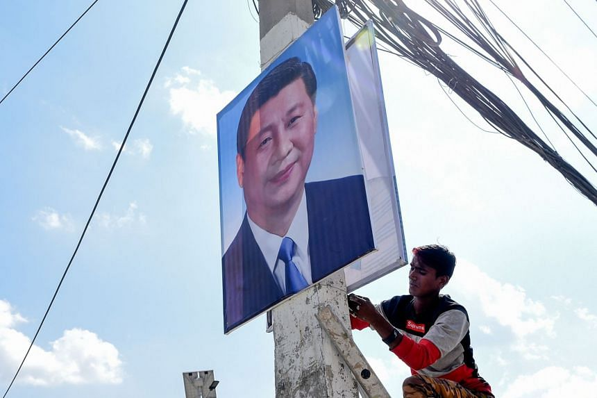 A worker hanging up a picture of Chinese President Xi Jinping ahead of his state visit in Kathmandu, Nepal, on Oct 11, 2019.