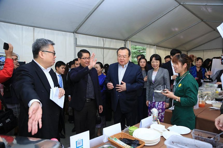 Singapore's Ambassador to China Stanley Loh (second from left) accompanying Deputy Director of the Central Foreign Affairs Commission Office Liu Jianchao (centre) and Chongqing Vice-Mayor Pan Yiqin (in grey) at the charity bazaar at the Singapore Emb