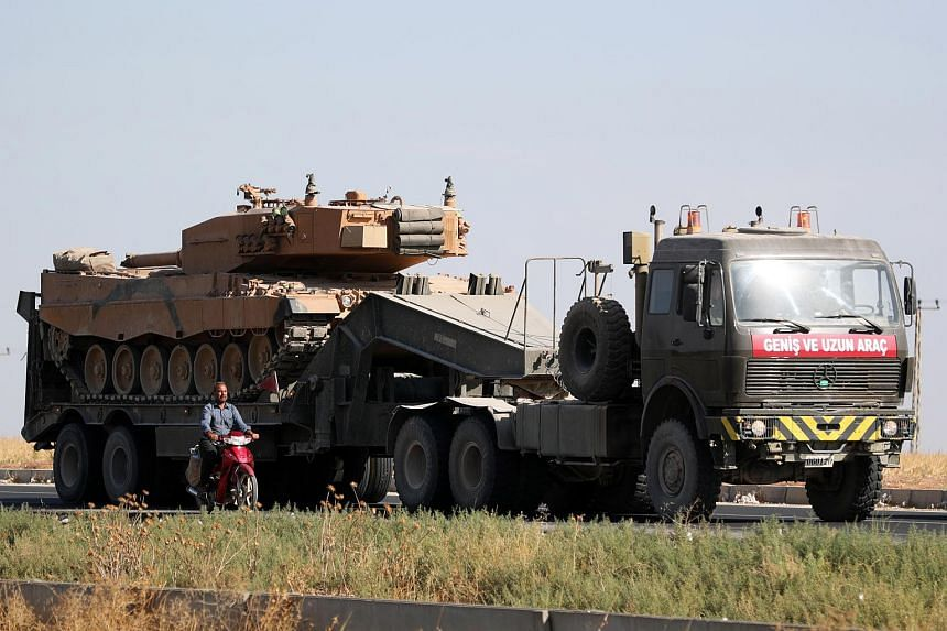 A Turkish tank is seen passing through Akcakale district on its way to the border with Syria during a military operation against Kurdish forces, in Sanliurfa, Turkey, on Oct 12, 2019.