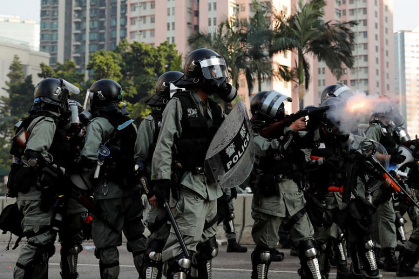 A riot police officer fires a tear gas canister during a demonstration on China's National Day, in Wong Tai Sin, Hong Kong on Oct 1, 2019.