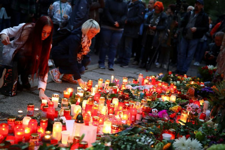 People place candles outside the synagogue in Halle, Germany on Oct 11, 2019, after two people were killed in a shooting.