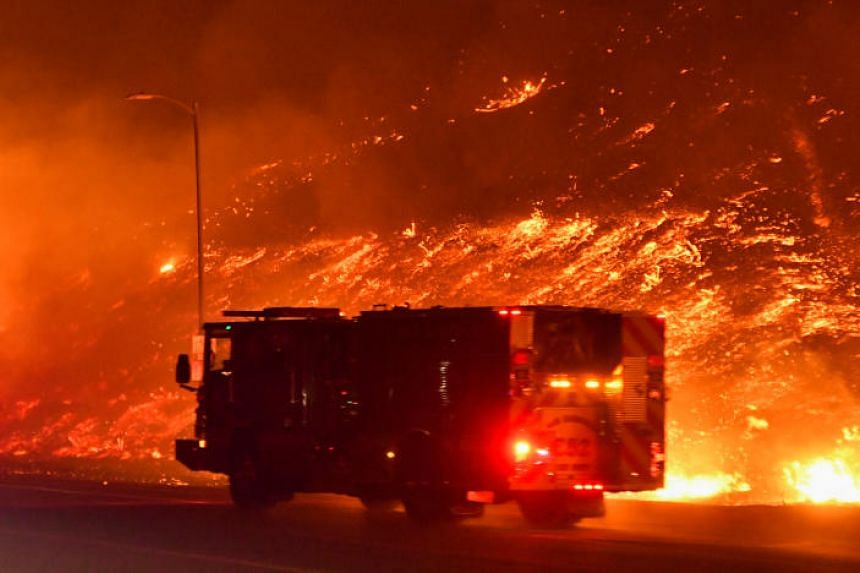 Firefighters battle a wind-driven wildfire in Sylmar, California, US, on Oct 11, 2019.