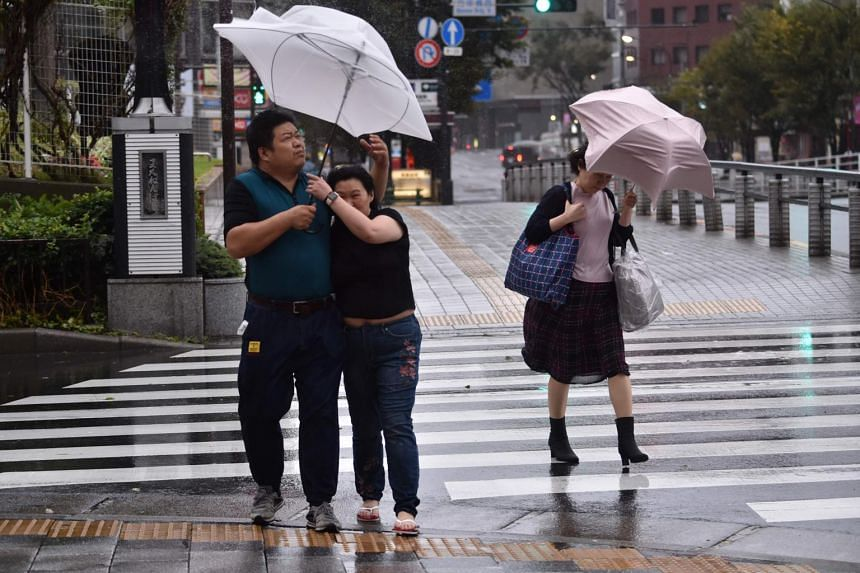 Pedestrians hold onto their umbrellas as rain falls amid strong winds in Tokyo, on Oct 12, 2019.