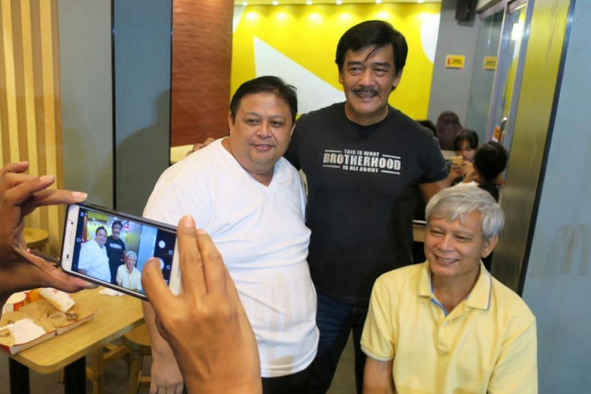 Sonny Parsons (centre), leader of Filipino boyband Hagibis, poses for a photo with fans at a fastfood restaurant in Manila, Philippines.