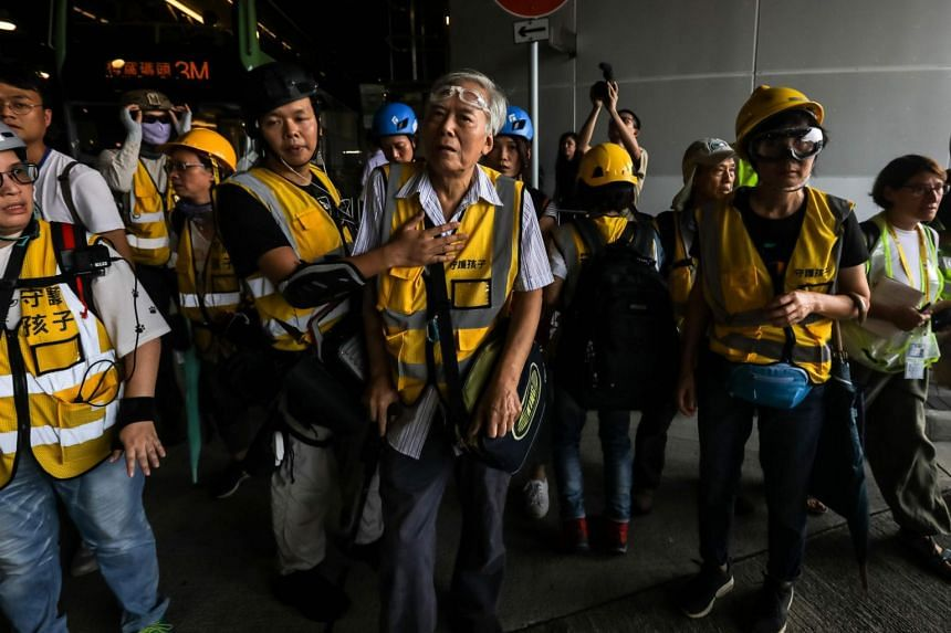 "Grandpa Wong (centre), 85, taking a rest with other ""silver hair"" volunteers after intervening in a confrontation between protesters and riot police in the Tung Chung district in Hong Kong, on Sept 7, 2019."