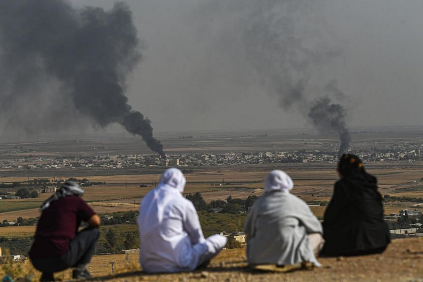 People look on as smoke rises from the Syrian town of Ras al-Ain, in a picture taken from the Turkish side of the border on Oct 11, 2019.